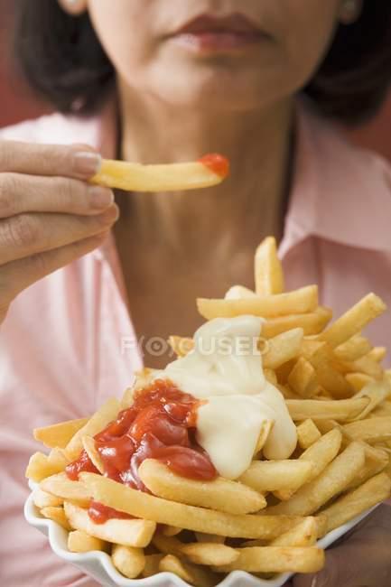 Женщина ест чипсы — стоковое фото