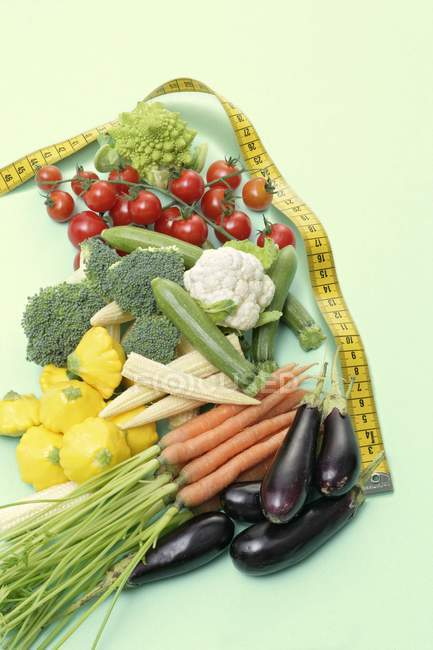 Assorted baby vegetables with tape measure on green surface — Stock Photo