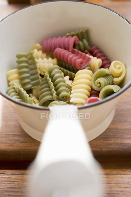 Closeup view of colored Riccioli pasta in strainer — Stock Photo