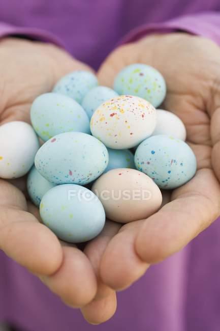Hands holding chocolate eggs — Stock Photo