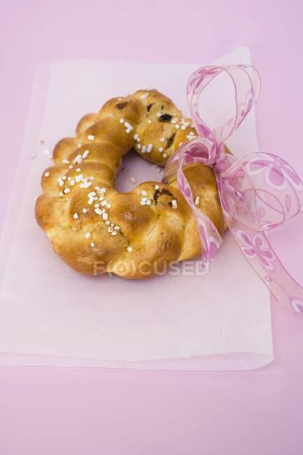 Vista de primer plano del anillo de pan trenzado con azúcar perla y arco rosa - foto de stock