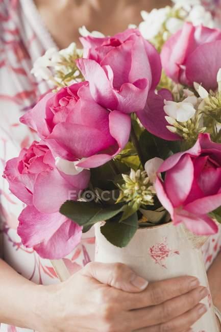 Primer plano vista recortada de la mujer sosteniendo jarrón de flores de verano - foto de stock