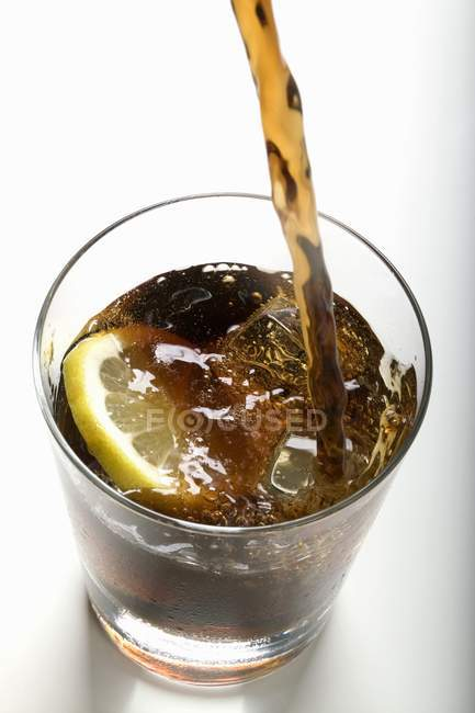 Pouring cola into a glass — Stock Photo