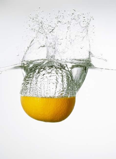 Orange falling into water — Stock Photo