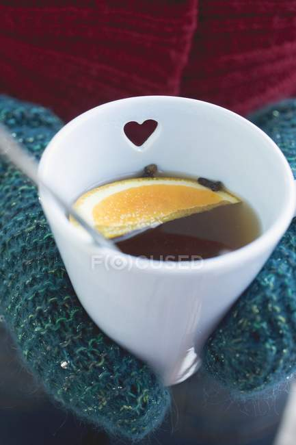 Hands in mittens holding hot punch — Stock Photo
