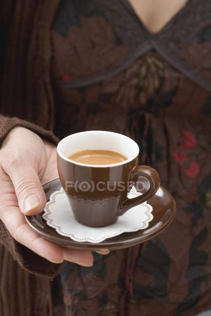 Woman holding cup of espresso — Stock Photo