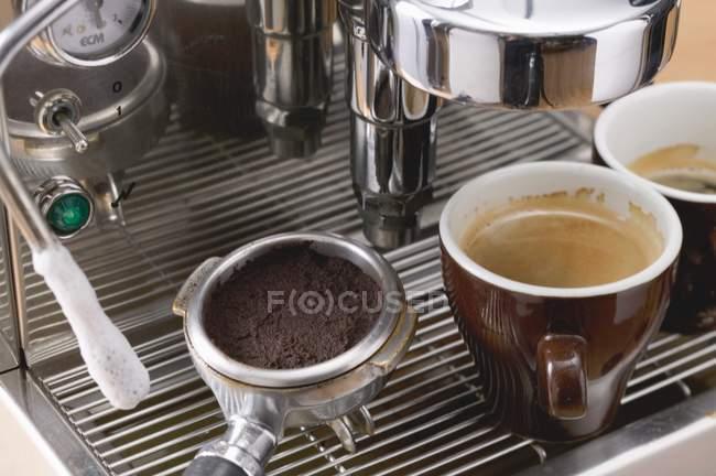Cups of espresso on coffee machine — Stock Photo