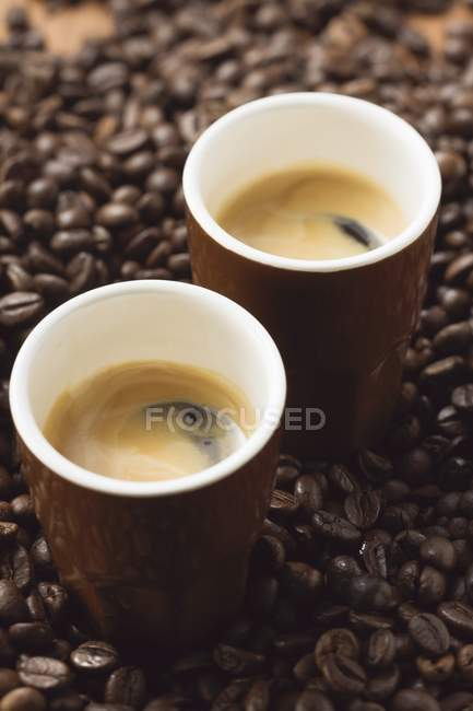 Espresso cups on coffee beans — Stock Photo