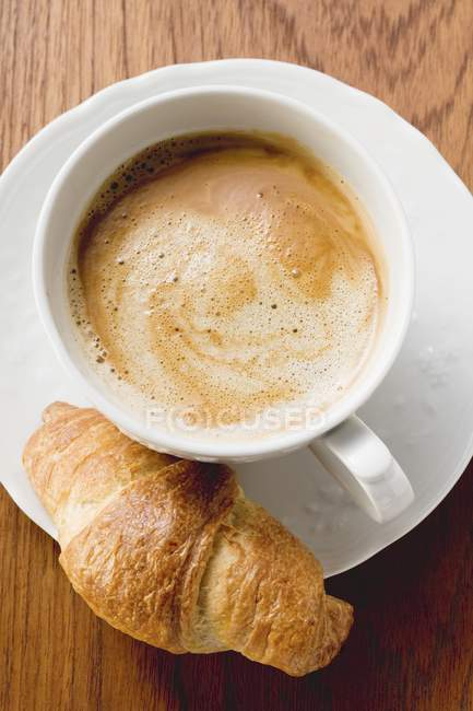 Croissant with cup of cappuccino — Stock Photo