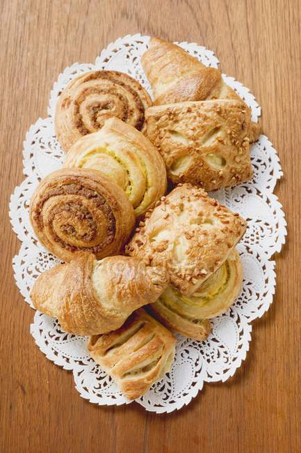 Top view of assorted Danish pastries on lace napkin and wooden surface — Stock Photo