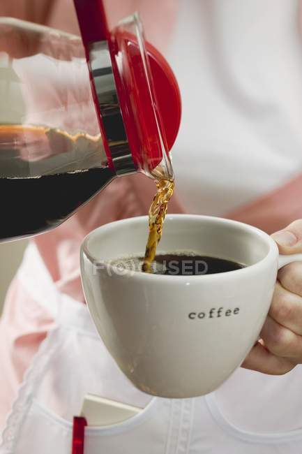 Female hands Pouring coffee — Stock Photo