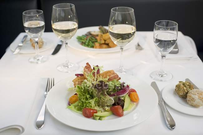Salad with bacon and glasses of wine — Stock Photo