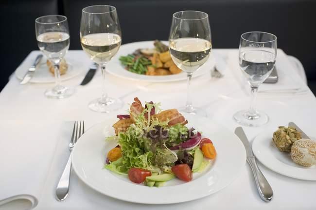 Salada com bacon e copos de vinho — Fotografia de Stock