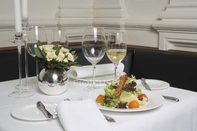 Крупный план салата и белого вина на накрытом столе в ресторане — стоковое фото