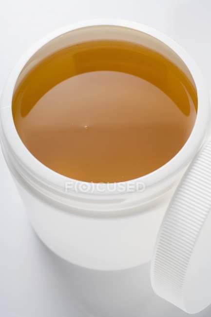 Honig im Plastikbehälter — Stockfoto