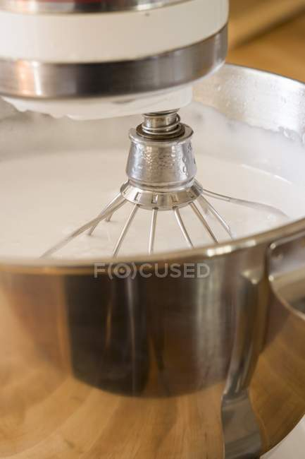Closeup view of cream in food mixer with balloon whisk — Stock Photo