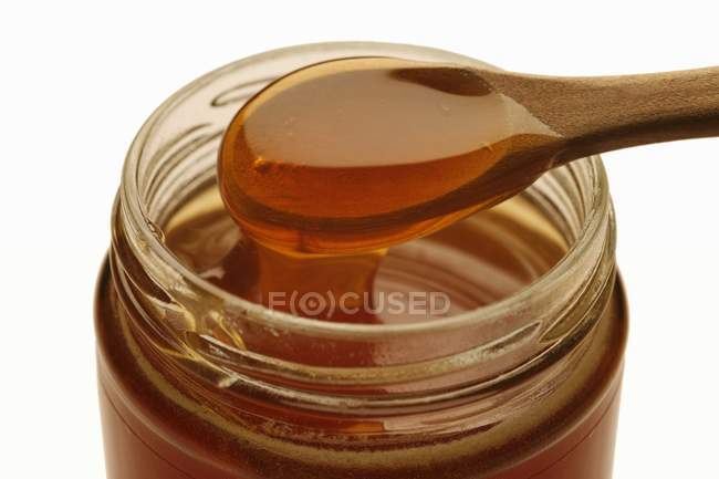Manuka honey running from spoon — Stock Photo