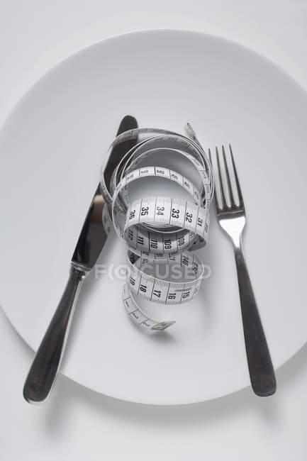 Vista superiore del coltello con forcella e misura di nastro sulla zolla bianca — Foto stock