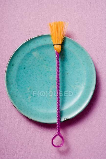 Closeup top view of colored pastry brush on blue plate — Stock Photo