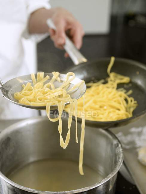 Cook putting pasta into pan — Stock Photo