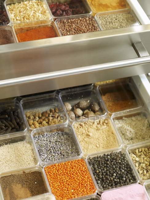 Vista elevada del cajón de especias con diferentes especias en envases - foto de stock