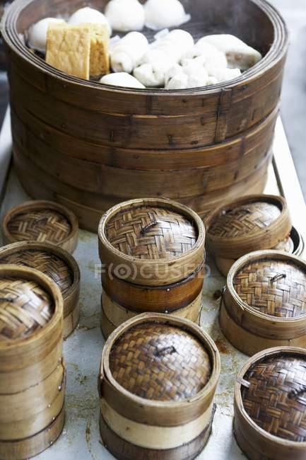 Cestas de vaporizar y varios tipos de dumplings chinos - foto de stock