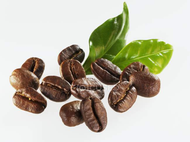 Roasted coffee beans with leaves — Stock Photo