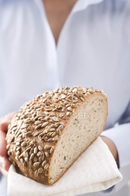 Femme tenant du pain de tournesol — Photo de stock