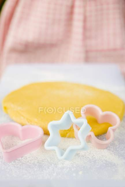 Vista de closeup de massa com farinha e biscoito cortadores — Fotografia de Stock