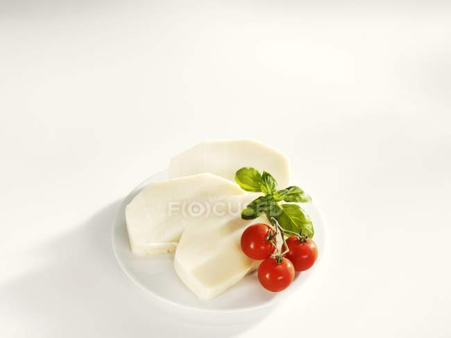 Slices of mozzarella on plate with tomatoes and basil — Stock Photo