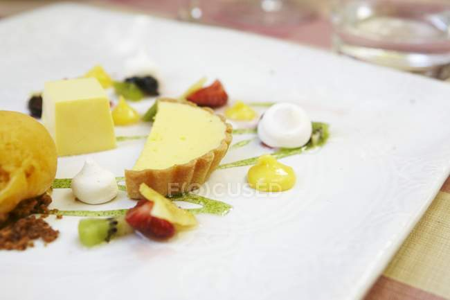 Closeup view of fruit dessert with cream and pastry on platter — Stock Photo