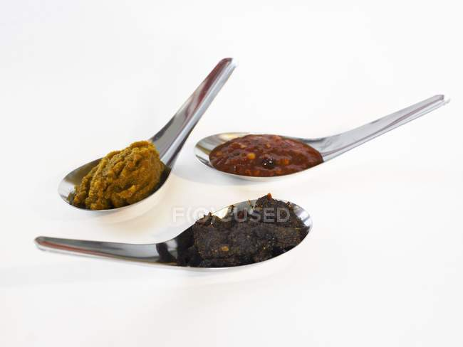 Closeup view of three Asian spice pastes on spoons — Stock Photo