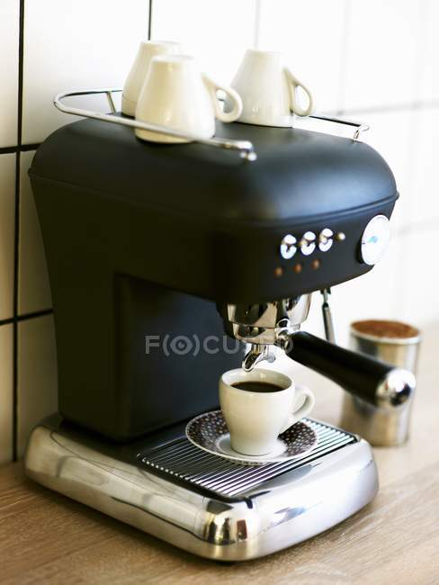 Cup of espresso on coffee machine — Stock Photo