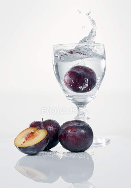 Closeup view of plum falling to glass of water — Stock Photo