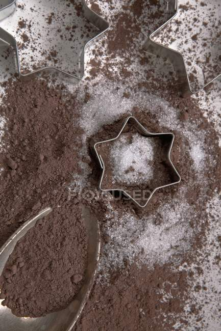 Closeup top view of cocoa powder on a silver spoon with sugar and biscuit cutters — Stock Photo
