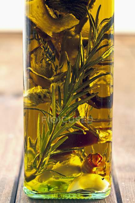 Closeup view of Porcini mushroom oil with herbs and rosemary — Stock Photo