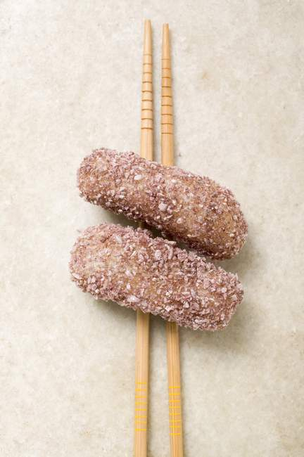 Closeup view of dumplings in coconut flakes on chopsticks — Stock Photo