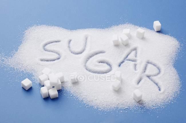 Vista elevada da pilha de açúcar com a palavra açúcar escrito nele — Fotografia de Stock