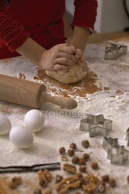 Criança amassar biscoito massa sobre uma superfície enfarinhada — Fotografia de Stock