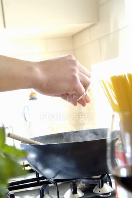 Detailansicht der Hände, die Zugabe von Gewürzen Zutaten in Pfanne — Stockfoto