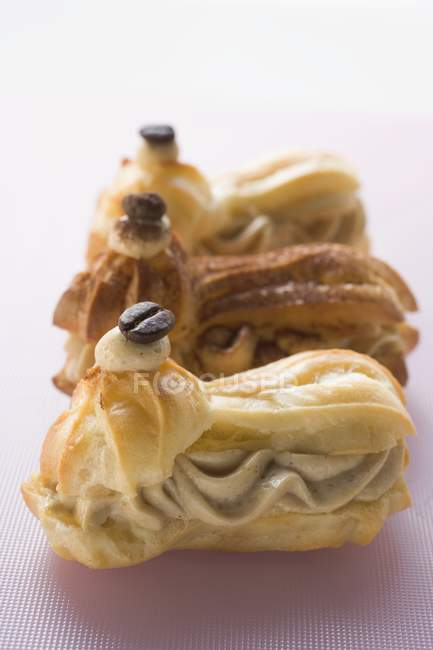 Closeup view of three eclairs filled with mocha cream — Stock Photo