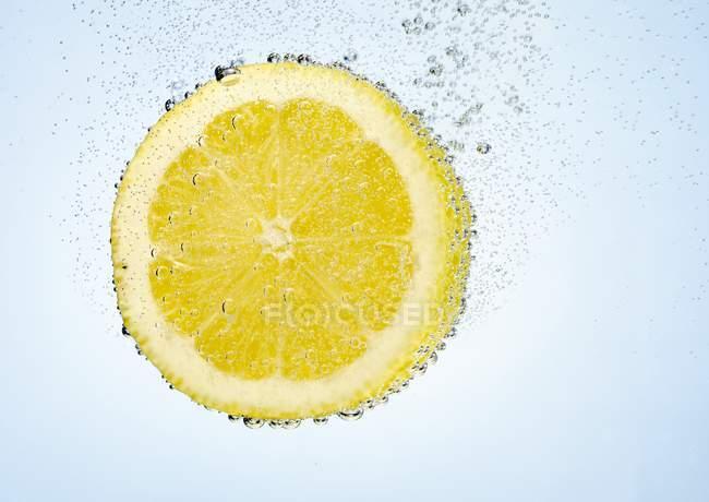 Zitronenscheibe in Wasser — Stockfoto