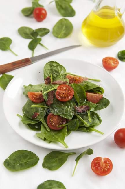 Салат из шпината с помидорами черри на белом фоне над скатерть — стоковое фото