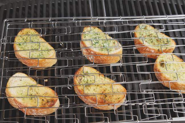 Grilled garlic baquettes on wire rack — Stock Photo