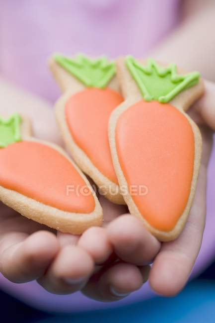 Manos sosteniendo galletas de Pascua - foto de stock