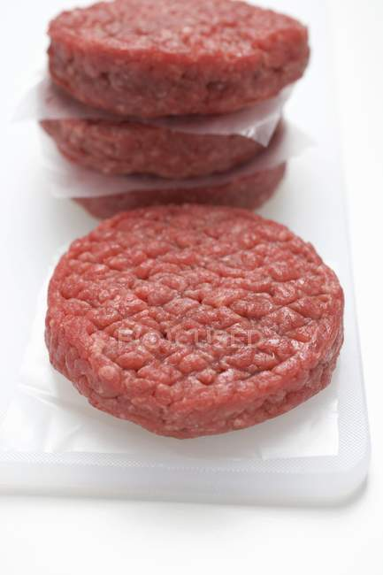 Raw burgers on white board — Stock Photo