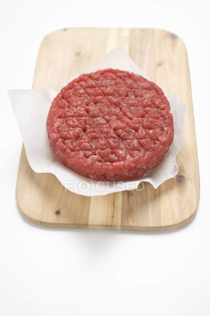 Raw burger on paper — Stock Photo