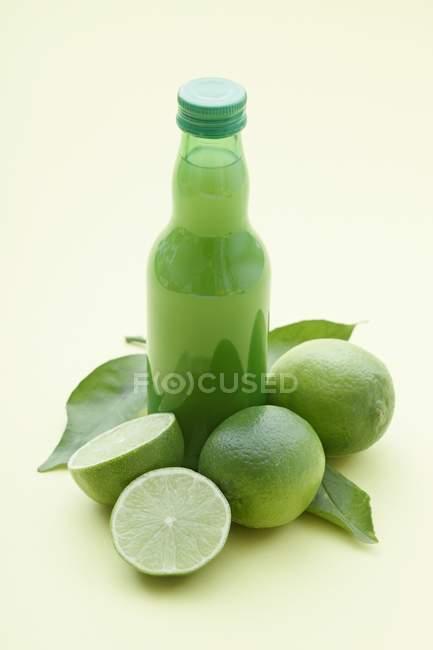 Garrafa de suco de limão e limas frescas — Fotografia de Stock