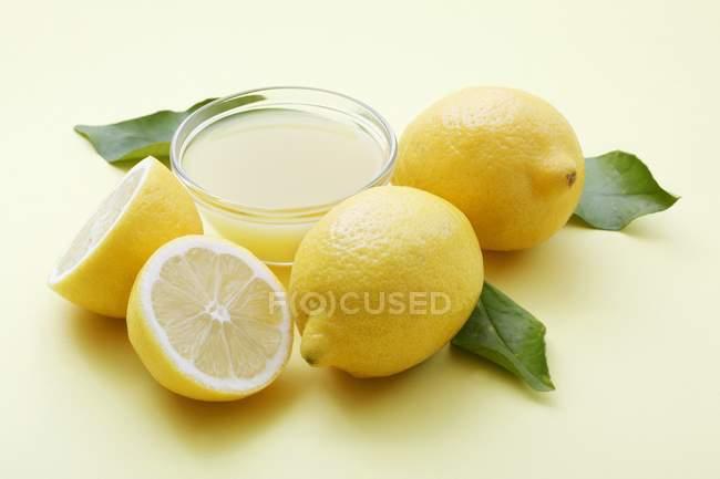 Schüssel mit Zitronensaft und frische Zitronen — Stockfoto