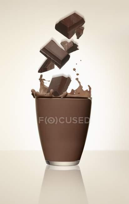Крупним планом подання шоколад штук падаючи на скло какао — стокове фото
